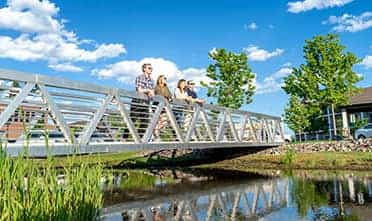 Four friends standing on the bridge and leaned over the railing, looking at something on a sunny day
