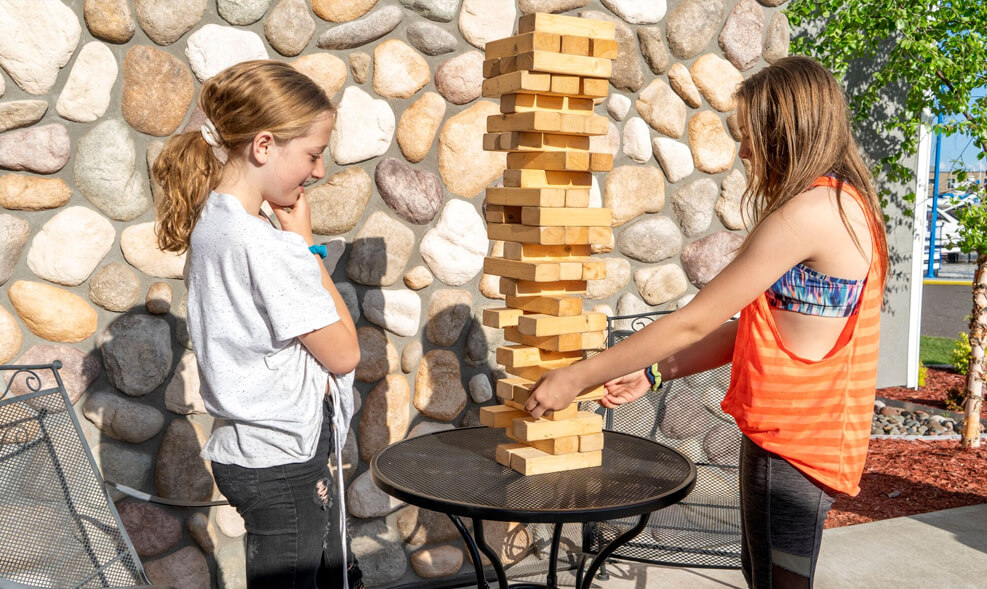 two kids are having a lot of fun with the building blocks outside of the resort on a sunny day