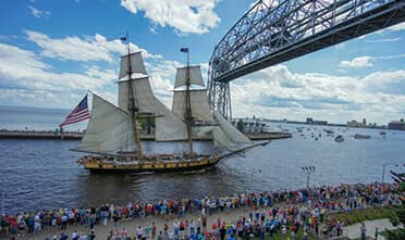 a treasure ship sailing under Duluth's Aerial Life Bridge and the shore is full of people