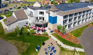 the overlook of Park Point Marina Inn taking from the sky with a group of people sitting outside