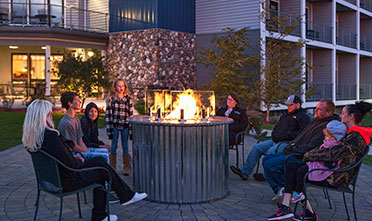 a group of people sitting in chairs facing the campfire in front of Park Point Marina Inn