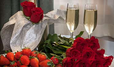 lovely strawberry and roses, two glasses of champagne putting on the table in romantic atmosphere