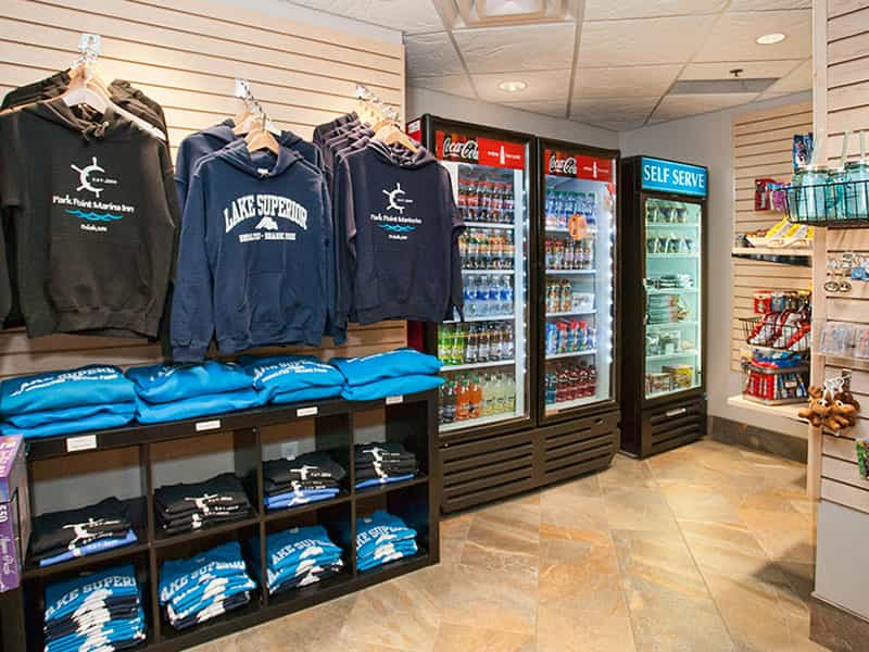 interior inside a gift shop including hoodie section and two filled fridge with different beverages
