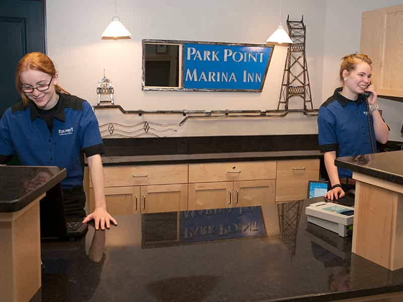 two staffs happily working on the front desk of Park Point Marina Inn while one picking up the phone