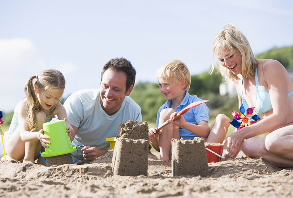parents having fun on the beach with their kids building up a king's castle in a mound of sand
