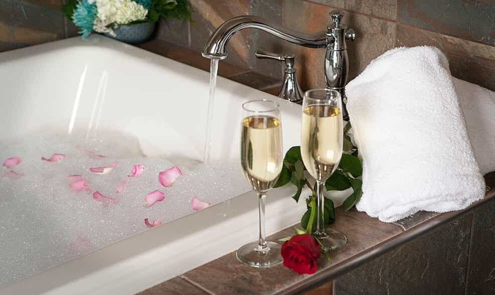 a bathtub with flowers floating on the water and two glasses of champagne are next to it
